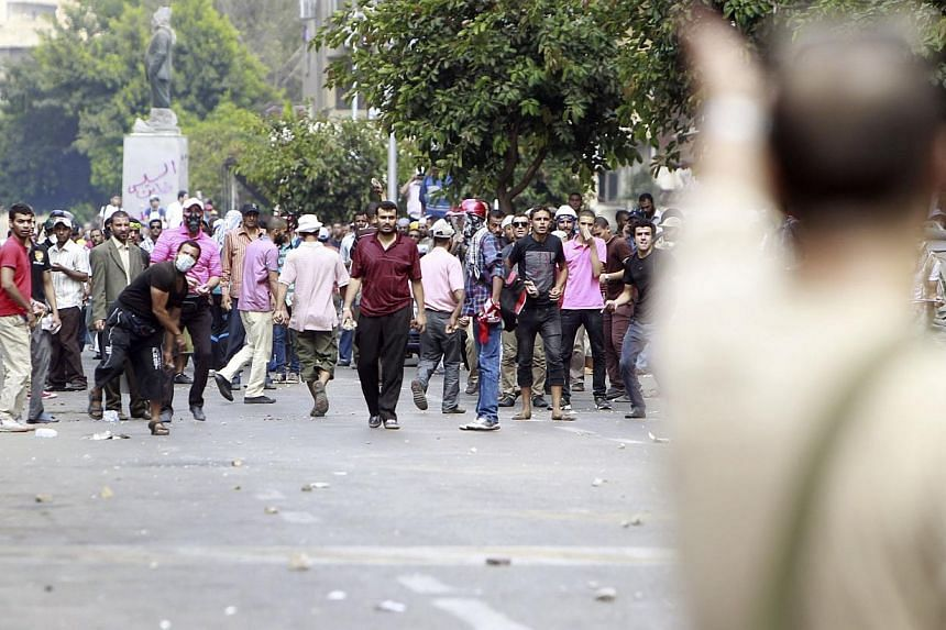 A local resident (foreground, on right) gestures towards supporters of ousted Egyptian President Mohamed Mursi during clashes in central Cairo on Aug 13, 2013. At least 17 people were killed on Wednesday, Aug 14, 2013, as police moved in to disperse