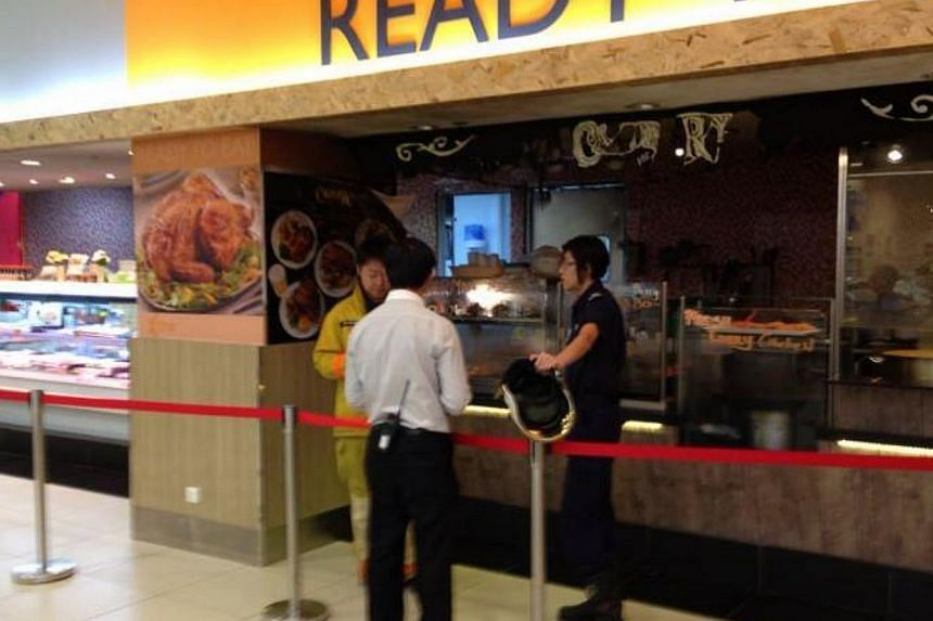 Three employees manning the Ready-to-Eat counter at the NTUC FairPrice Xtra store in Jem shopping centre suffered minor burns when a deep fryer caught fire on Wednesday morning. -- PHOTO: LEE JIAN XUAN
