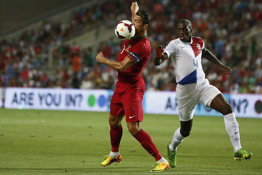 Portugal's Cristiano Ronaldo (left) attempts to control the ball near the Netherlands' Bruno Martins Indi during their international friendly soccer match at Algarve stadium near Faro on Aug 14, 2013. A late Ronaldo tap-in salvaged a 1-1 home draw fo