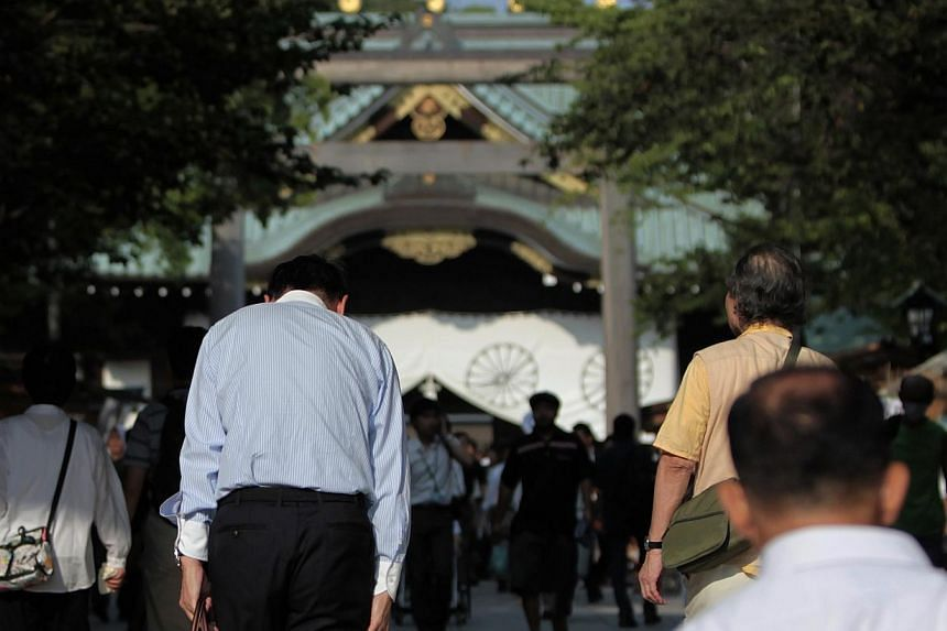 A visitor bows to pay tribute at the gate of the Yasukuni Shrine in Tokyo on Aug 15, 2013, to mark the 68th anniversary of Japan's surrender in World War Two. -- PHOTO: REUTERS