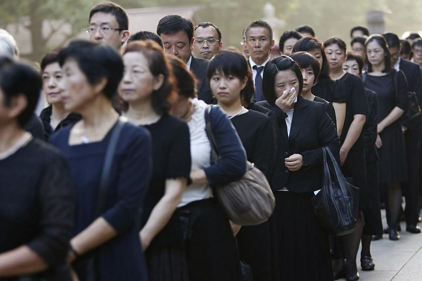 People dressed in black queue up to pay tribute at the gate of the Yasukuni Shrine in Tokyo on Aug 15, 2013, to mark the 68th anniversary of Japan's surrender in World War Two. -- PHOTO: REUTERS