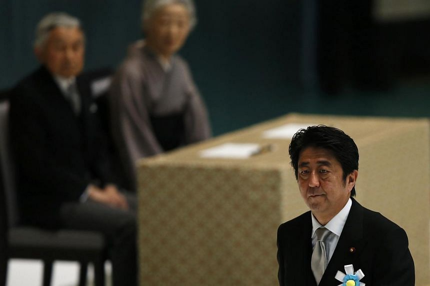 Japan's Prime Minister Shinzo Abe (right) walks past Japan's Emperor Akihito (left) and Empress Michiko during a memorial service ceremony marking the 68th anniversary of Japan's defeat in World War Two, at Budokan Hall in Tokyo on Aug 15, 2013. -- P
