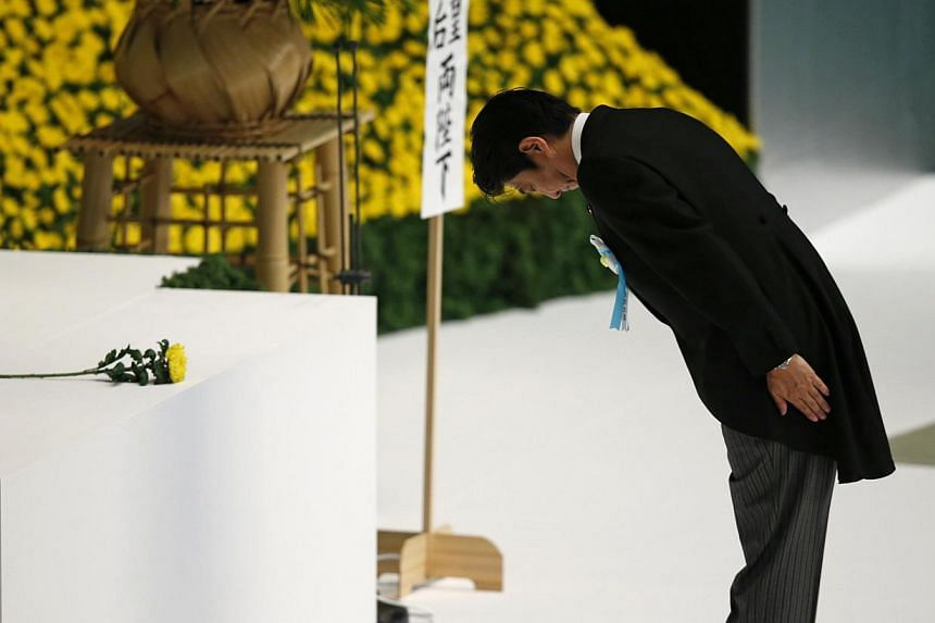 Japan's Prime Minister Shinzo Abe bows after offering a chrysanthemum flower during a memorial service for those who died in World War Two, during a ceremony marking the 68th anniversary of Japan's defeat in the war, at Budokan Hall in Tokyo on Aug 1