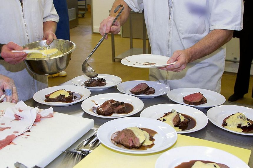 """Inmates from Rimutaka prison putting together """"Savannah Grass-fed Beef Fillet"""" for the """"Wellington on a Plate"""" festival in the Upper Hutt area of Wellington on July 30, 2013. -- FILE PHOTO: AFP"""