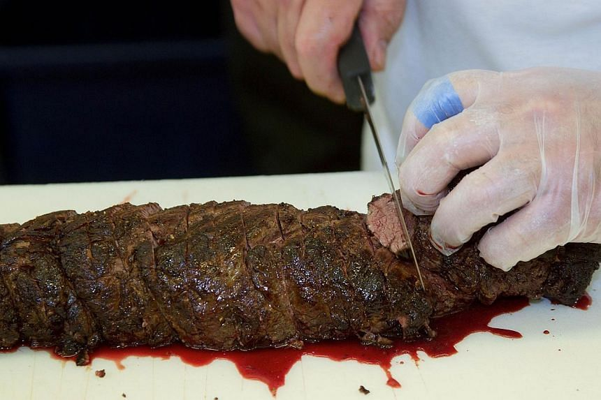 """An inmate from Rimutaka prison carving beef at the """"Wellington on a Plate"""" festival in the Upper Hutt area of Wellington on July 30, 2013. -- FILE PHOTO: AFP"""