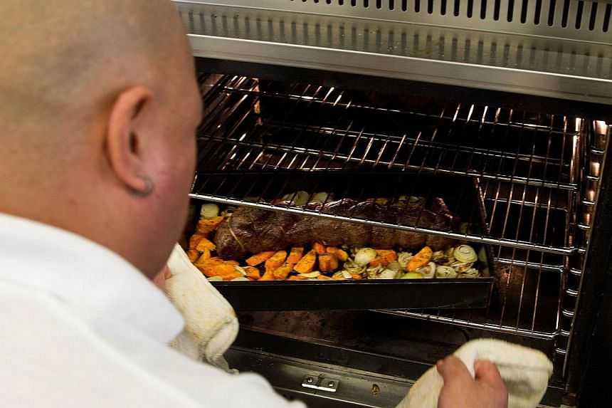 """An inmate from Rimutaka prison checking a dish in the oven as they put on a fine dinning experience at the """"Wellington on a Plate"""" festival in the Upper Hutt area of Wellington on July 30, 2013. -- FILE PHOTO: AFP"""