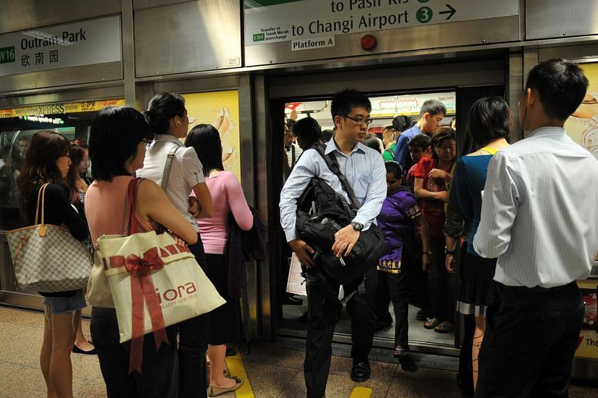 Train services along the East West Line were delayed for nearly 30 minutes, and not an hour as earlier reported, causing massive overcrowding at MRT stations during the morning rush hour on Thursday. -- ST FILE PHOTO: JOYCE FANG