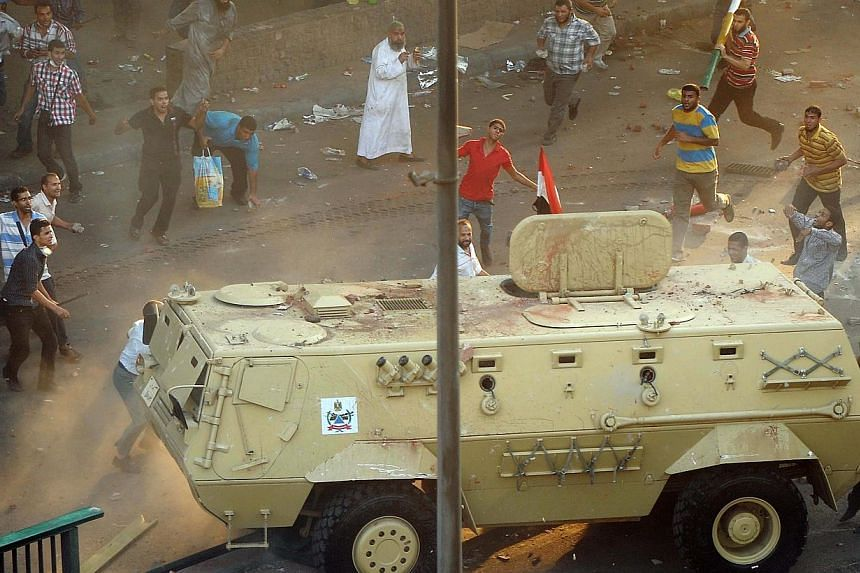 Supporters of ousted Islamist President Mohamed Mursi capture an Egyptian security forces vehicle at the Ministry of Finance in Cairo, Egypt, on Aug 14, 2013. Egyptian security forces crushed the protest camps of thousands of supporters of the depose