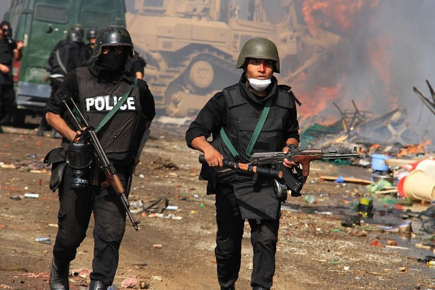 Egyptian security forces clear a sit-in camp set up by supporters of ousted Islamist President Mohamed Mursi in Nasr City district, Cairo, Egypt, on Aug 14, 2013. Egyptian security forces crushed the protest camps of thousands of supporters of the de