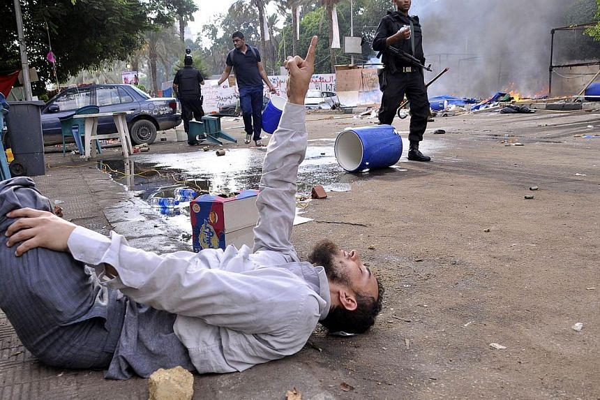 A protester lies on the ground as Egyptian security forces disperse supporters of Egypt's ousted President Mohamed Mursi in a huge camp in Cairo's Al-Nahda square on Aug 14, 2013. Egyptian security forces crushed the protest camps of thousands of sup
