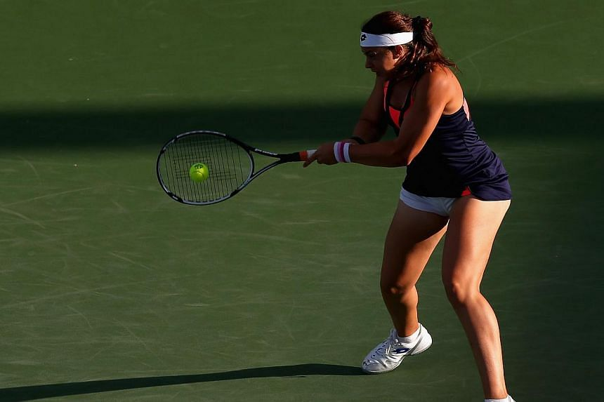 Marion Bartoli of France returns a shot while playing against Simona Halep of Romania during the Western & Southern Open on Aug 14, 2013, at Lindner Family Tennis Center in Cincinnati, Ohio. Wimbledon champion Bartoli shocked the tennis world on