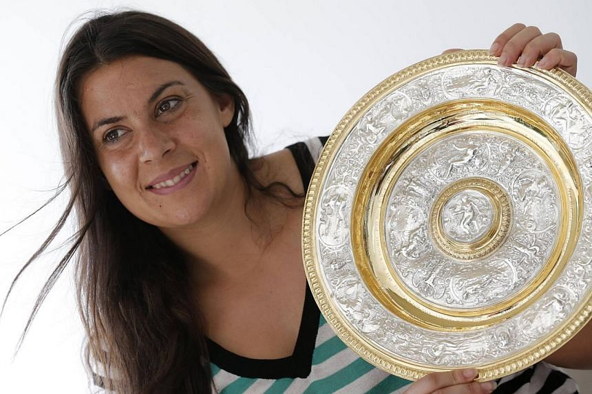 Wimbledon women's singles tennis champion Marion Bartoli of France holds her trophy as she attends an interview with Reuters in Boulogne-Billancourt near Paris, on July 9, 2013. Bartoli shocked the tennis world on Aug 14 by announcing her retirement