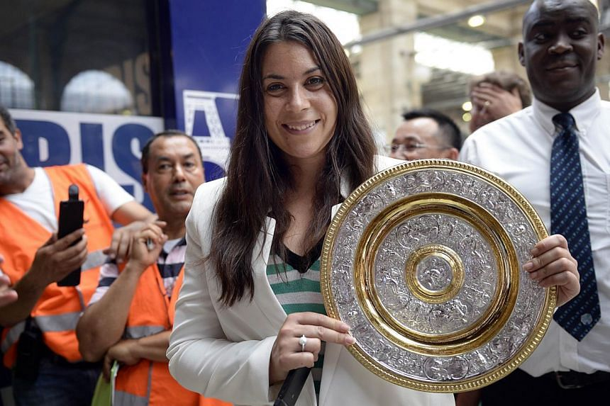 French tennis player Marion Bartoli poses with her 2013 Wimbledon trophy upon her arrival from Wimbledon at Paris Gare du Nord on July 9, 2013. Bartoli shocked the tennis world on Aug 14 by announcing her retirement from the sport at the age of 28. -