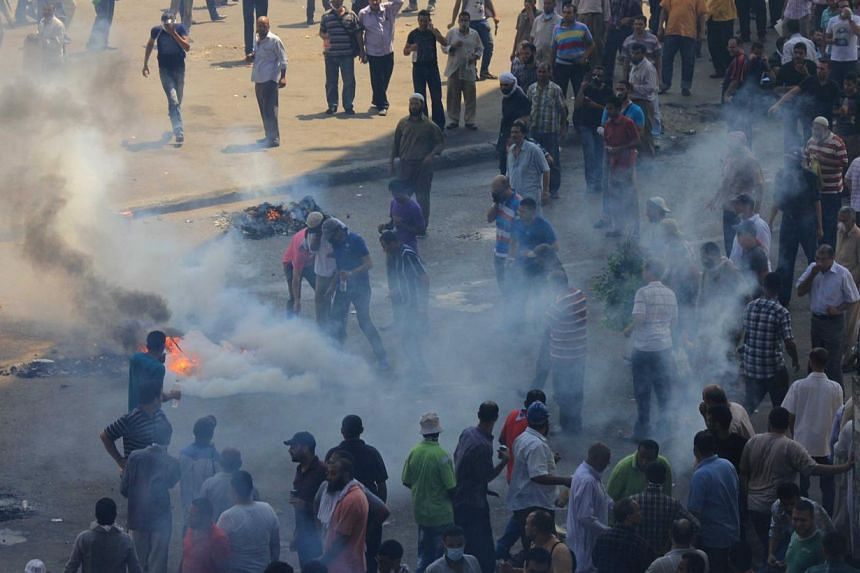 Supporters of Egypt's ousted President Mohamed Mursi clash with security forces in the eastern Nasr City district of Cairo, Egypt, on Aug 14, 2013. Egyptian security forces crushed the protest camps of thousands of supporters of Mr Mursi on Wednesday