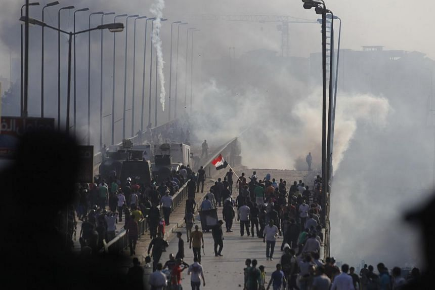 Members of the Muslim Brotherhood and supporters of ousted Egyptian President Mohamed Mursi flee from tear gas and rubber bullets fired by riot police during clashes, on a bridge leading to Rabba el Adwia Square where they are camping, in Cairo on Au