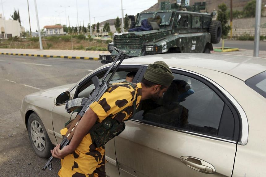 """A policeman looks into a car at a checkpoint at one of the entrances to the British embassy in Sanaa on Aug 14, 2013. The British embassy in Yemen will be open in the """"next couple of days"""", the ambassador said on Thursday, Aug 15, 2013, as she return"""