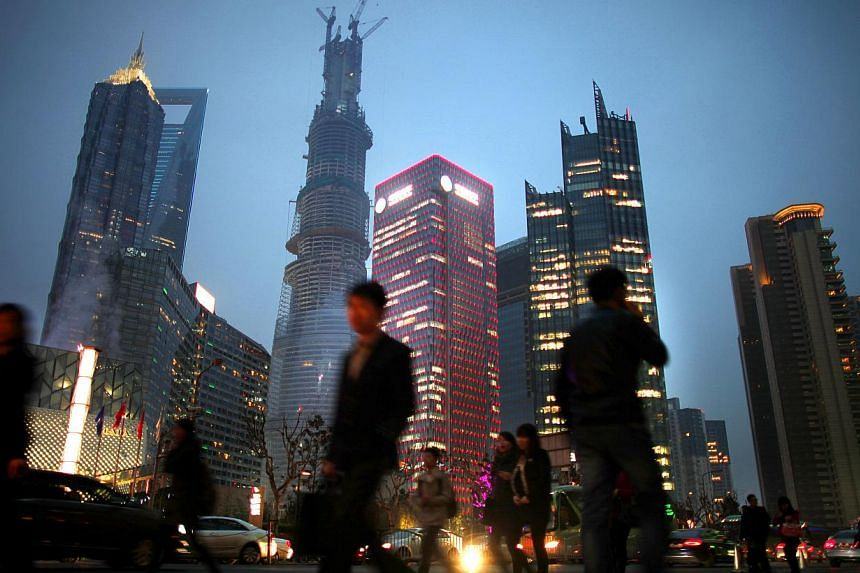 People walk along a busy street at Pudong financial district in Shanghai, on March 27, 2013. China's millionaires, a symbol of the country's growing wealth, increased at their slowest rate in five years in 2012 as the economy and stock market stumble