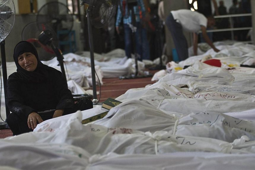 An Egyptian woman mourns over the body of her daughter wrapped in a shroud at a mosque in Cairo on Aug 15, 2013,following a crackdown on the protest camps of supporters of ousted Islamist president Mohamed Mursi the previous day. Egypt's