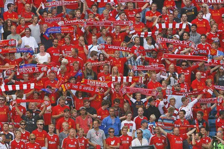 Liverpool supporters hold up their team scarves prior to the kick-off of a friendly soccer match between Valerenga and Liverpool at Ullevaal Stadium in Oslo, Aug 7, 2013. Football fans who have signed up for English Premier League (EPL) packages