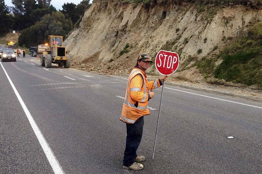 A man holds a traffic sign as workmen clear rubble from a road after the side of a hill collapsed following an earthquake on the outskirts of the town of Seddon in the Marlborough region, on New Zealand's South Island on Aug 16, 2013. Police said the