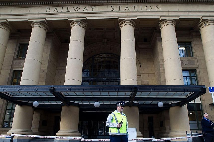 Police guard the Wellington railway station to stop people from entering as trains stopped working after a 6.5 earthquake hit central New Zealand on Aug 16, 2013. Police said they had received no reports of significant injury or damage. -- PHOTO: AFP