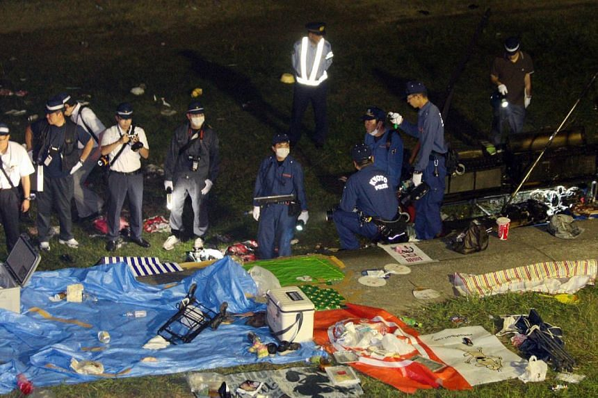 Police investigators inspect an explosion site caused by a gas cylinder at Fukuchiyama in Kyoto prefecture on on Aug 15, 2013. More than 50 people were injured on Thursday evening by an explosion probably caused by a gas cylinder just before a firewo