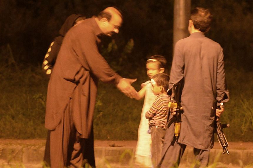 Mr Zamurd Khan (left), a leader of opposition Pakistan Peoples Party, shakes hands with the child of a gunman (right) before capturing him during a stand-off with police in Islamabad on Aug 15, 2013. Pakistani police snipers shot and seriously wounde