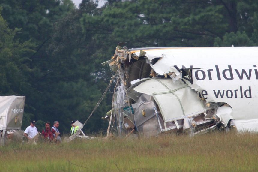 Investigators work the scene of the UPS cargo plane that crashed Wednesday on approach to the Birmingham-Shuttlesworth International Airport Thursday, Aug. 15, 2013 in Birmingham, Ala.An initial investigation into the wreckage of the UPS cargo