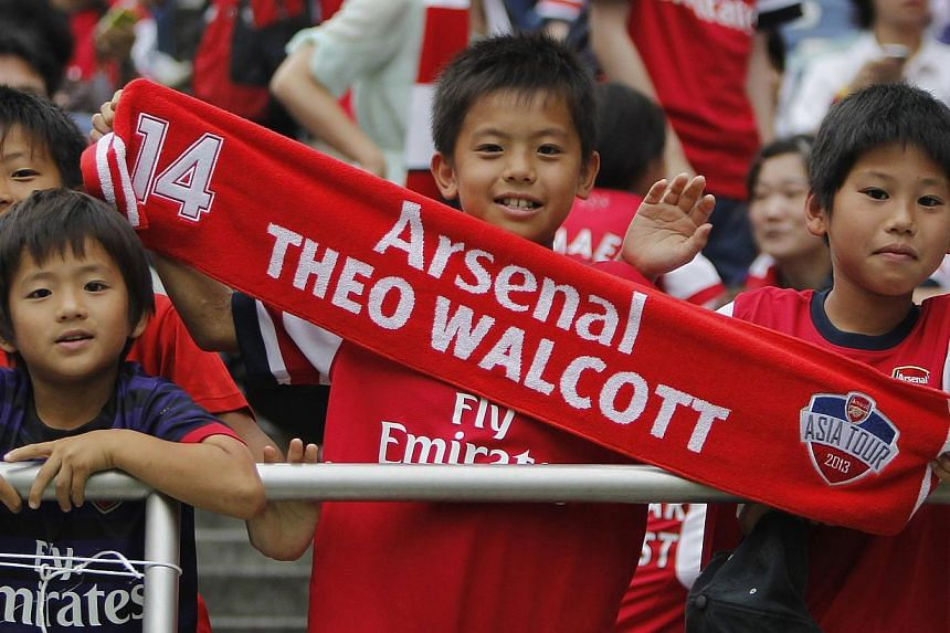 An Arsenal fan holds a muffler before a soccer friendly match against the Urawa Reds as part of Arsenal's Asia tour 2013 in Saitama, north of Tokyo, July 26, 2013. SingTel mio TV subscribers will get to watch a free preview of English Premier League