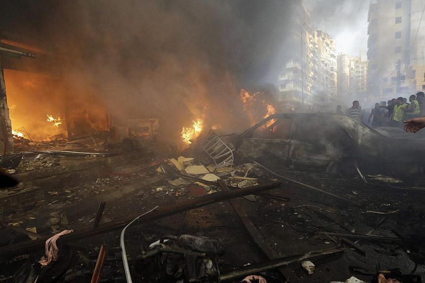 Burnt cars and shops are seen at the site of a car bomb explosion in southern Beirut, Lebanon, on Thursday, Aug. 15, 2013. The powerful car bomb ripped through a southern Beirut neighborhood that is a stronghold of the militant group Hezbollah on Thu