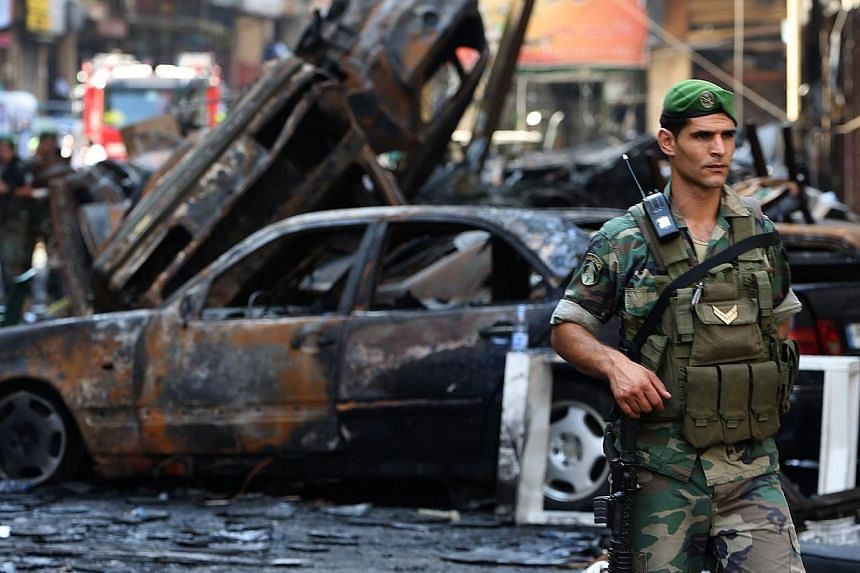 A Lebanese army soldier passes in front of burned cars at the site of a car bomb explosion, in the southern suburb of Beirut, Lebanon, Friday, Aug 16, 2013. The death toll from a car bomb which ripped through the southern Beirut stronghold of Lebanon