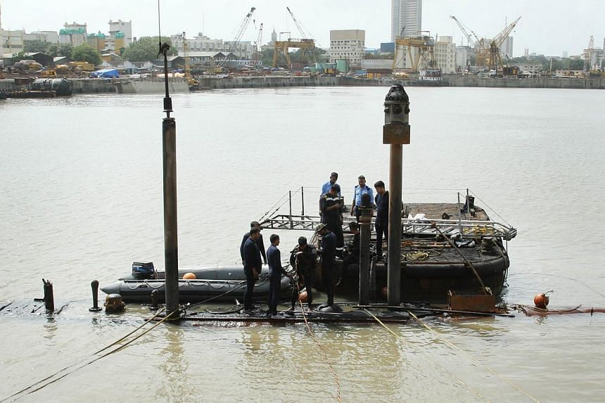 Navy divers standing on the INS Sindhurakshak submarine prepare to dive into the waters of the Arabian Sea, during a rescue operation in Mumbai, Aug 14, 2013. India's navy on Friday retrieved three badly burned bodies from a submarine that exploded i