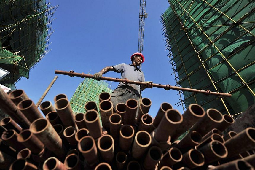A labourer moves a steel pipe at a residential construction site in Fuzhou, Fujian province, July 4, 2013. The European Union, fresh from solving one major trade dispute with China, has called for the World Trade Organisation to rule on another over