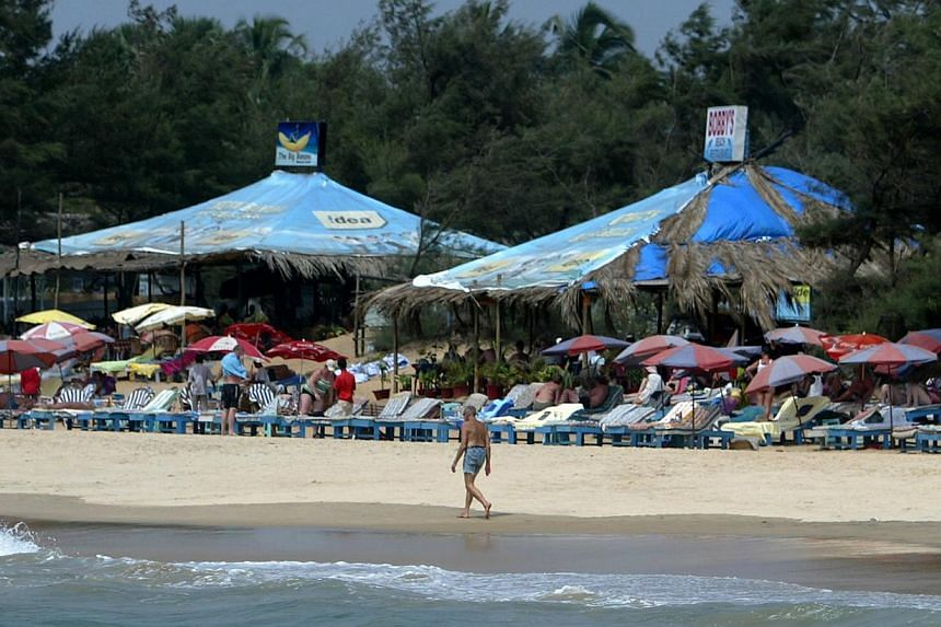 A tourist walks past a row of sunbeds on Baga Beach in Goa. India's popular holiday state of Goa has announced a ban on dance bars, further restricting the party scene in a destination once famous as a raver's paradise. -- FILE PHOTO: AFP