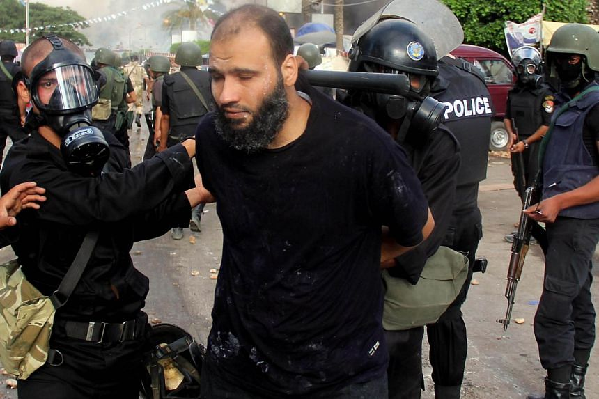 Egyptian riot police arrest a demonstrator in Cairo's Al-Nahda square on Aug 14, 2013, as they dispersed supporters of Egypt's ousted President Mohamed Mursi in two huge protest camps in the Egyptian capital. Egyptian police arrested 1,004 alleged su