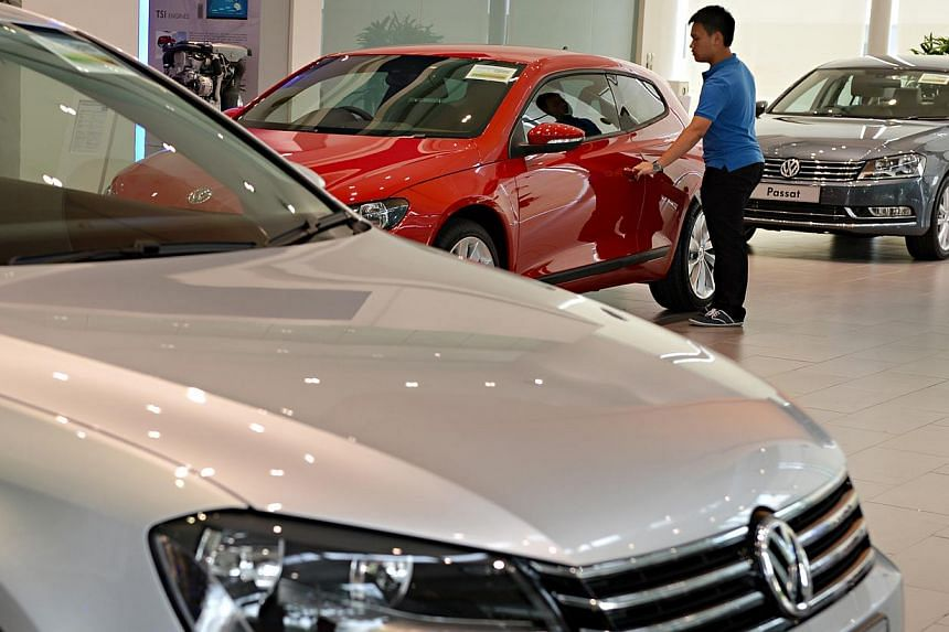 A visitor checking out a car at the Volkswagen Centre showroom on 23 Dec 2012. In a bid to rev up business squeezed by loan curbs introduced six months ago, motor firms are starting to roll out no-frills car leasing plans which require lower monthly