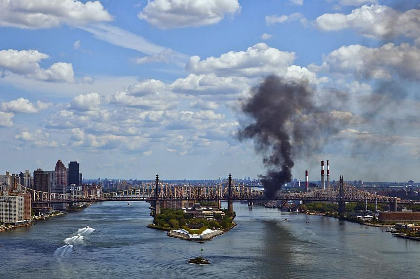 A cloud of smoke billows from the Ed Koch Queensboro Bridge, as seen from Waterside Plaza, on the east side of New York, on Aug 16, 2013. Traffic on a much-used bridge into Manhattan suffered major delays on Friday when a truck caught fire midway acr