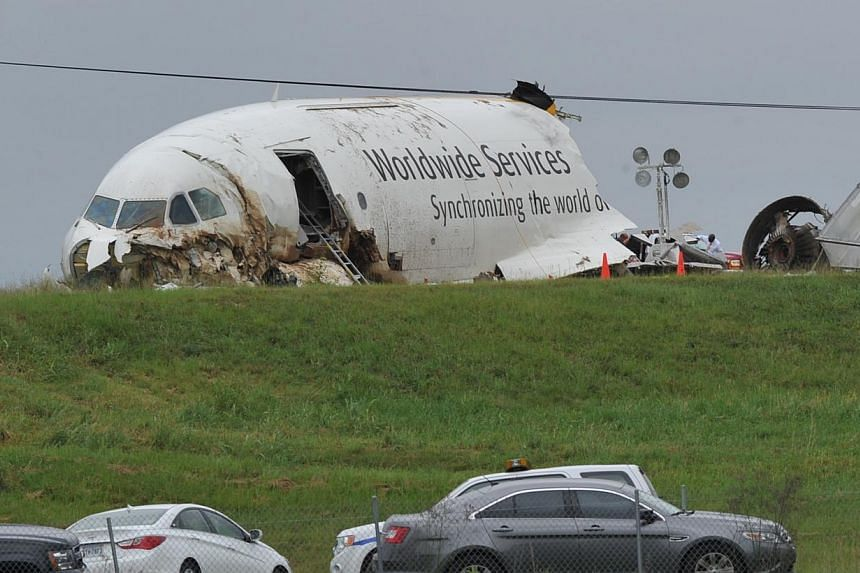 The National Transportation Safety Board and Federal Bureau of Investigation scour the field north of the Birmingham-Shuttlesworth International Airport, where UPS flight 1354 crashed on Wedesday, in this photo taken on Aug 16, 2013 in Birmingham, Al