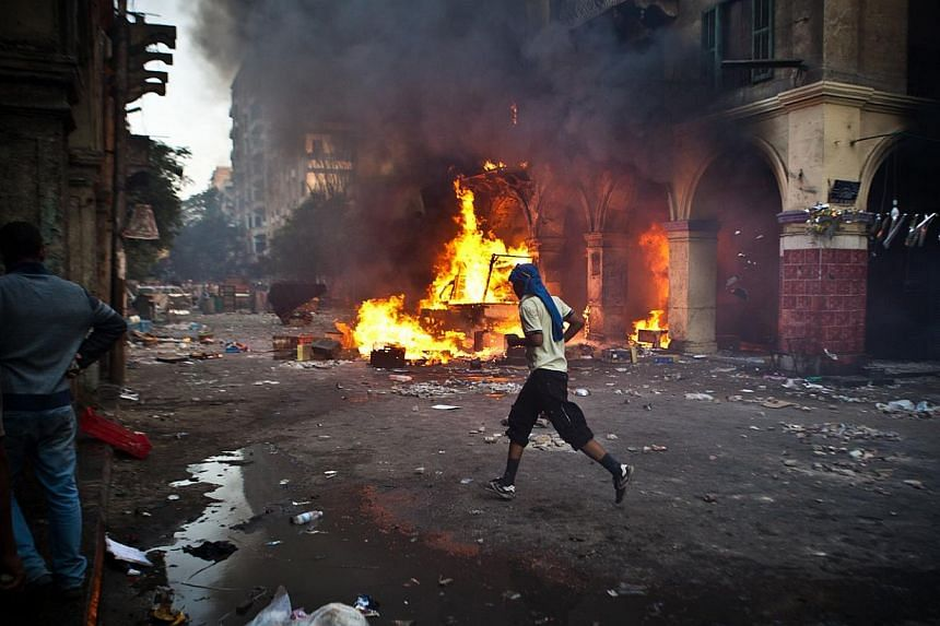 A supporter of the Muslim Brotherhood and of ousted President Mohamed Mursi runs past a burning vehicle during clashes with security officers close to Cairo's Ramses Square on Aug 16, 2013. Egypt's tourism industry was facing meltdown on Friday as fo