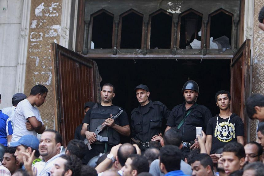 Police officers stand guard at one of the doors to Fath mosque at Ramses Square in Cairo on Saturday, Aug 17, 2013. Gunmen and members of the Egyptian security forces exchanged fire on Saturday at a Cairo square where dozens of supporters of Mr