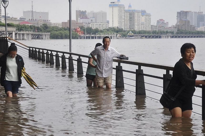 People wade through a flooded street near the overflowing Songhua River in Harbin, Heilongjiang province on Friday, Aug 16, 2013.Twenty-five people have been killed by floods which hit north-eastern China over the past week, state media said on
