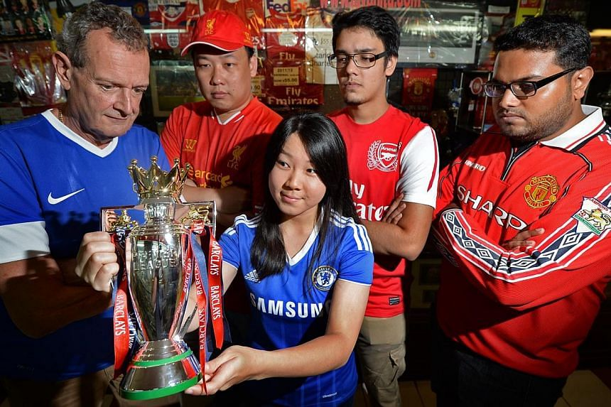 Chelsea fan Cindy Chew, 26, gets her hands on the EPL trophy, watched by (from left) Everton supporter Keith Bayliss, 57; Liverpool fan Henry Han, 37; Arsenal fan Raun Anand, 22; and Manchester United fan R. Surendran, 30. The ST microsite is running