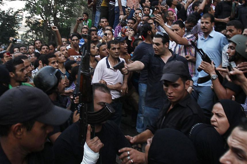 A plain clothes policeman (centre) points his gun as security forces escort Muslim Brotherhood members through supporters of the interim government installed by the army from the Al-Fath mosque on Ramses Square in Cairo on Aug 17, 2013. Around 1