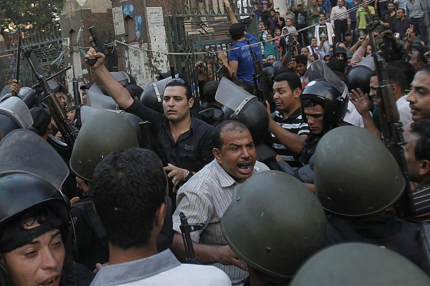 A plain clothes policeman points his gun as security forces escort Muslim Brotherhood members through supporters of the interim government installed by the army from the Al-Fath mosque on Ramses Square in Cairo on Aug 17, 2013.Around 10,000 peo