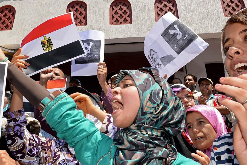 Moroccan protestors hold Egyptian flags as they chant slogans during a rally in Rabat against the violence in Egypt and in support of Egypt's ousted president Mohamed Mursi on Aug 16, 2013.Around 10,000 people took part in a demonstration in th