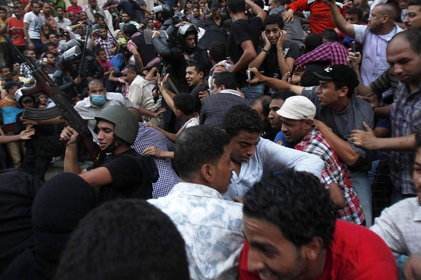 Police shoot in the air as they escort Muslim Brotherhood members through supporters of the interim government installed by the army from the Al-Fath mosque on Ramses Square in Cairo on Aug 17, 2013.Around 10,000 people took part in a demonstra