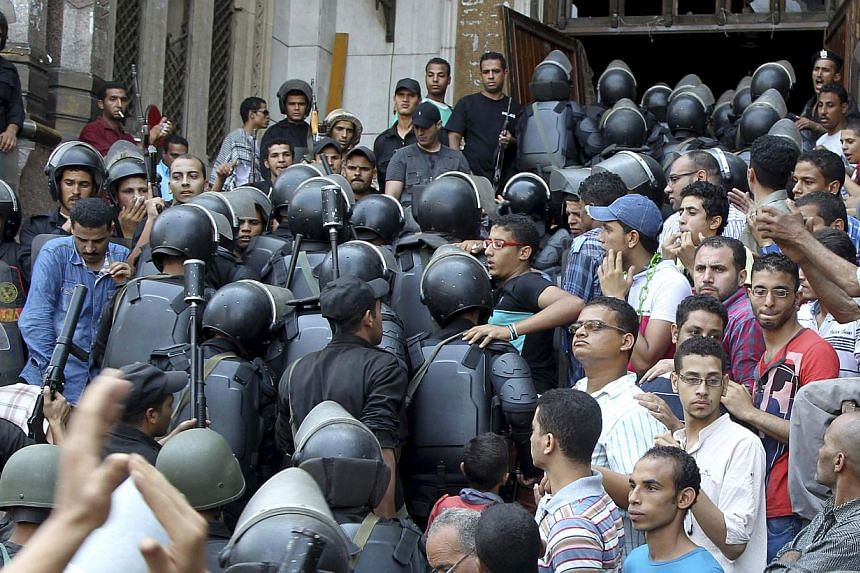 Policemen move into a mosque during clashes with supporters of deposed Egyptian President Mohamed Mursi inside a room of the al-Fath mosque in Cairo on Aug 17, 2013. Egyptian Islamists announced fresh demonstrations for Sunday after police ended a te