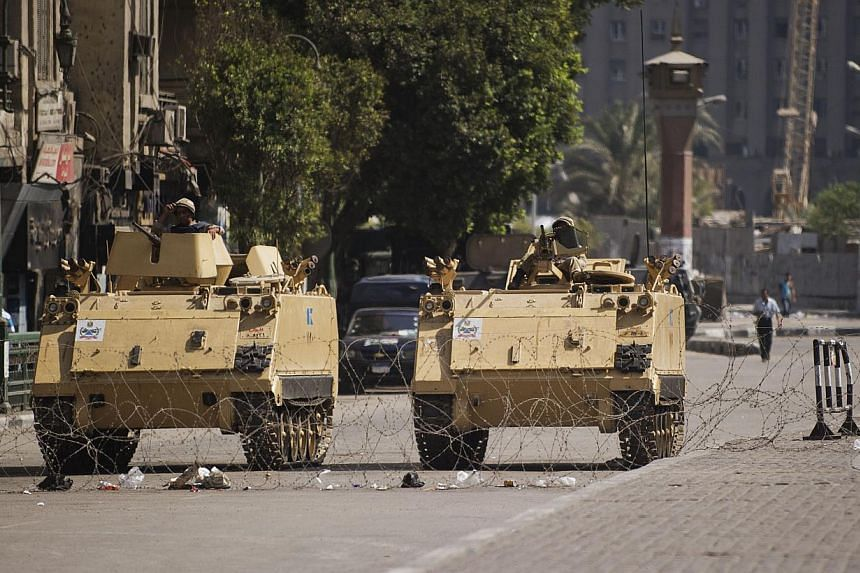 Egyptian army's armoured personnel carriers (APC) are seen stationed at the entrance of Tahrir Square in Cairo on Sunday, Aug 18, 2013. An Islamist alliance opposed to the Egyptian military's ouster of president Mohamed Mursi called off rallies that