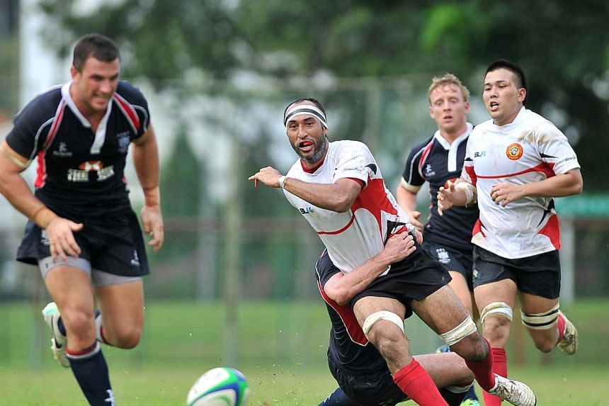 Daniel Marc Chow (centre in white), captain of the singapore rugby team, being tackled by a Hong Kong 'A' selection squad member, consisting of top players from its domestic league, during the Tri-Nations campaign on Sunday, Aug 18, 2013. Singapore s
