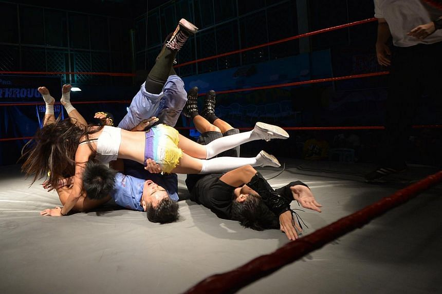 Ms Lee aka Alexis Lee (above) executing a body slam on male opponents (from left) Ng Yi Xun, Caleb Tan and Pan Jia De last night at Kampong Ubi CC. -- ST PHOTOS: ALPHONSUS CHERN